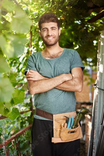 Close Up Portrait Of Young Good Looking Bearded Gardener With Garden Tools Smiling Standing