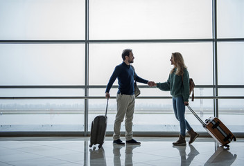 Two smiling adults saying goodbye before flying to foreign countries. They are shaking their hands and holding suitcases beside them. Copy space in left side