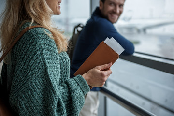 Female and male people preparing for the flight. Focus on woman holding wallet and tickets