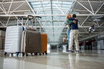 Low angle of happy man and woman hugging tight after a long separation. Focus on luggage