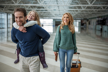 Wall Mural - Smiling family of tourists walking to the airplane. Focus on father carrying kid piggyback. Mother is beside them