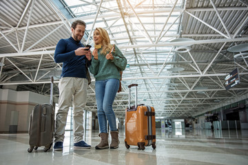 Low angle of happy couple using modern technology to purchase electronic ticket for plane. Their suitcases standing near. Copy space in right side