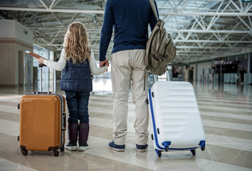 Wall Mural - Dad and child preparing for the flight. They are having tickets and baggage ready. Focus on back