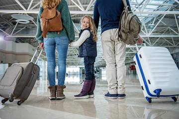 Happy female child and her parents arriving after visiting relatives abroad. Girl is turning around and smiling. Low angle
