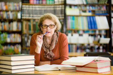 An elderly woman preparing for the exam in the library looking at camera