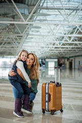 Portrait of happy embracing mother and kid in the airport terminal. Child is sitting on her lap