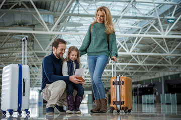 Full length of smiling family with suitcases going abroad. Father and daughter are looking at documents