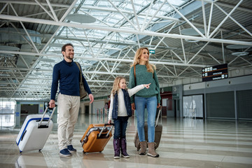 Cheerful parents and their daughter standing with luggage at the airport. Kid is pointing with finger