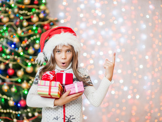 Happy little girl holding many gift boxes and pointing away.Space for text