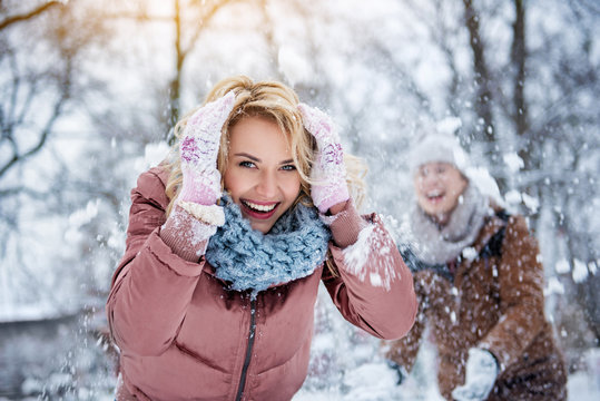 Waist up portrait of excited young woman covering her head from snow by hands. She is looking at camera and smiling. Man is throwing snowball on her on background
