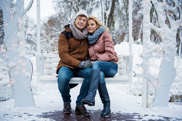 Full length portrait of cute loving couple sitting on bench and hugging. They are looking at camera and smiling. Winter romance concept