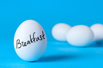 Healthy and nutritious breakfast of eggs. A positive start to the day. Chicken eggs and the word breakfast on a blue background