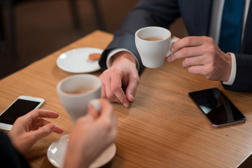Close up man arm keeping cups of delicious coffee. He situating at desk with colleague. Business break concept