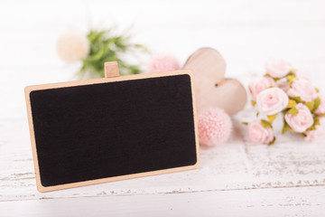 Small blank chalkboard for Valentine's or mother woman day. Background with pink roses.