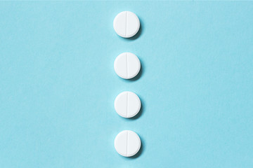 White pills on a blue background. Medications. Flat lay. Concept medicine