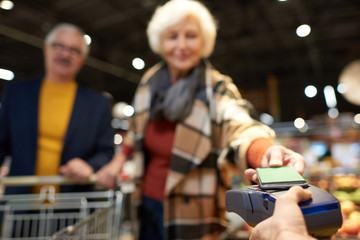 Portrait of modern senior couple buying groceries in supermarket paying with NFC payment via smartphone, focus on foreground, copy space