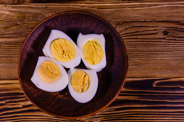 Ceramic plate with peeled boiled eggs on wooden table. Top view