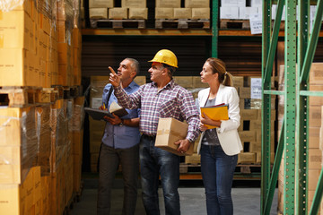 Two customs managers and warehouse worker checking list and inventory on the shelf in storehouse.
