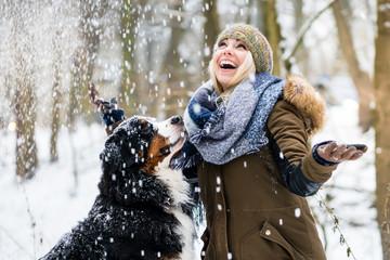 Frau geht Gassi mit ihrem Berner Sennenhund im Winter im Schnee