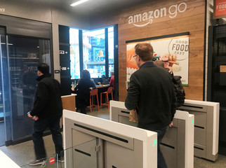 A customer walks out of the Amazon Go store, without needing to pay at a cash register due to cameras, sensors and other technology that track goods that shoppers remove from shelves and bill them automatically after they leave, in Seattle