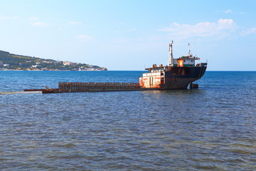 Unknown semi-submerged rusted and destroyed barge stranded in a bay