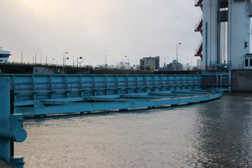 Barrier is closing and goes into the water at the Algerakering, large water barrier to protect the land below sealevel behind it in Krimpen aan den IJssel, The Netherlands