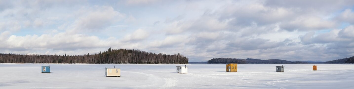 Panorama of wooden shelters for ice fishing on a frozen lake