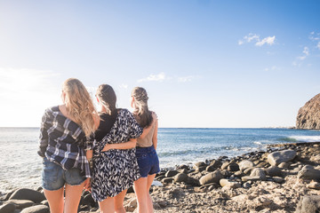Three young beautiful woman looking at the horizon. Back pint of view.