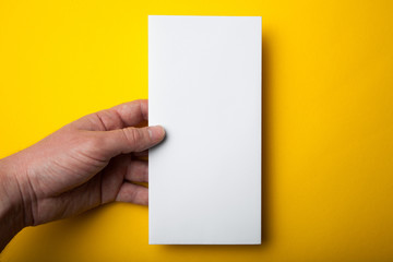 White DL flyer in hand on a yellow background. Empty mock-up.