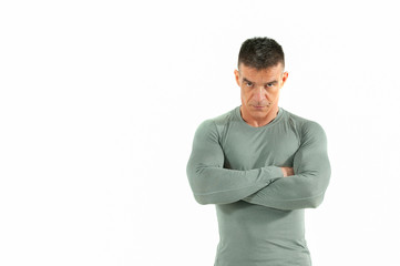 Angry muscular man with big muscles in tight shirt with crossed hands look at camera with anger in his eyes