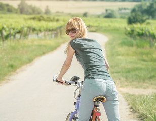 girl on bike in countryside rear view