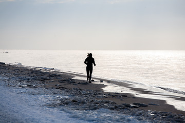 silhouette young fit woman is jogging running on a snow on the beach in winter. Sport and fitness