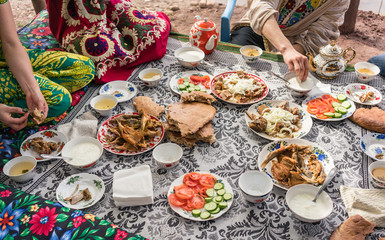Lots of traditional foods of Tajikistan on a restaurant table, people are eating