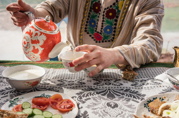 Young man in traditional clothing of Tajikistan pouring tea in restaurant