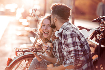 Couple in love joking together on a bench