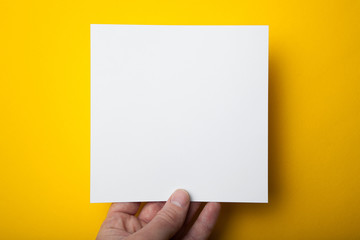 A square layout of a white paper in a hand on a yellow background.