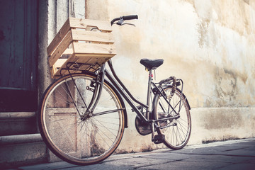 Foto auf Leinwand Fahrrad vintage bicycle with wooden crate, bike leaning on a wall in italian street