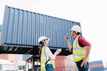 Asian foreman control loading Containers box and staff woman checking container box on forklift for Logistic Import Export in dock