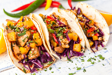 Mexican pork tacos with vegetables and pumpkin. Tacos on wooden white rustic background. Top view.
