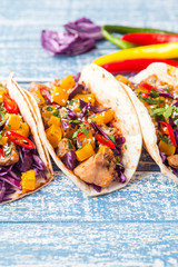 Mexican pork tacos with vegetables and pumpkin. Tacos on wooden blue rustic background. Top view.