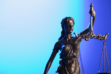 Gavel and themis on blue background.