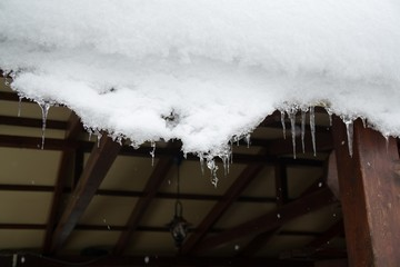 Icicles hanging from roof covered by snow in winter. Slovakia