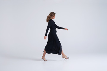 Woman wearing long black dress walking