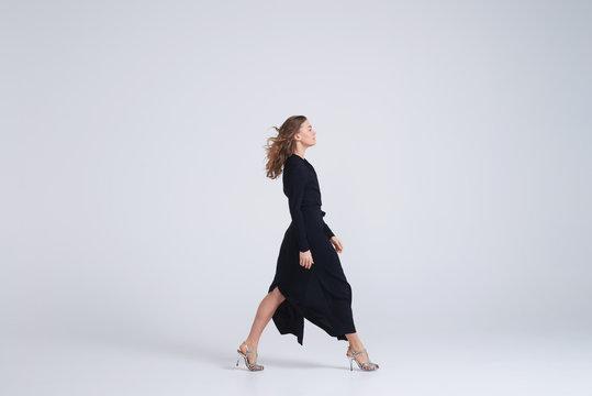 Woman model walking in trend black dress