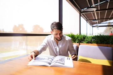 Graphic designer reading catalog at cafe.