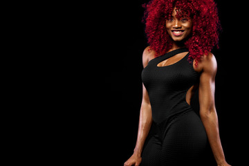 A strong athletic woman on black background wearing in sportswear, fitness and sport motivation. Sport concept with copy space.