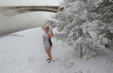 Lyubov Valiyeva, member of the Cryophile winter swimmers club, sprinkles herself with snow from branches of a pine on a bank of the Yenisei River, in Krasnoyarsk