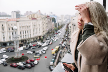 Portrait of beautiful young stylish blonde woman wearing beige coat and walking through the city streets. Trendy casual outfit. Street fashion.