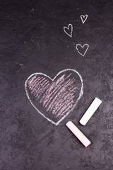 Chalk drawing of pink heart on the blackboard.