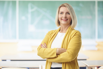 Female teacher in the classroom. Lovely female teacher looking at camera and smiling while standing with arms crossed in the classroom against the chalkboard.